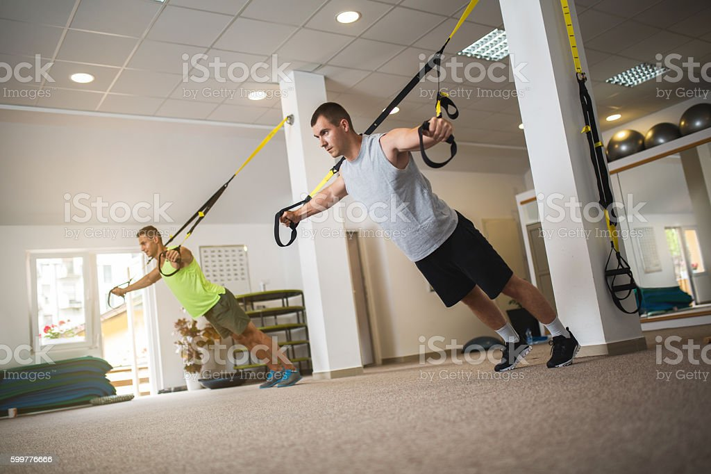 Athletic man exercising with suspension straps in health club. stock photo