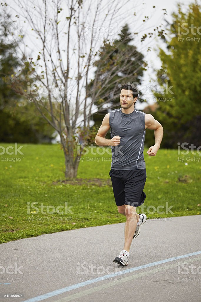 Athletic man grey fitness sportswear running in the park stock photo