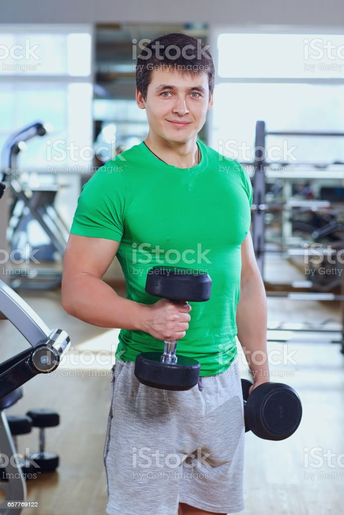 Athletic man in a green t shirt with dumbbells  the hands of spo stock photo