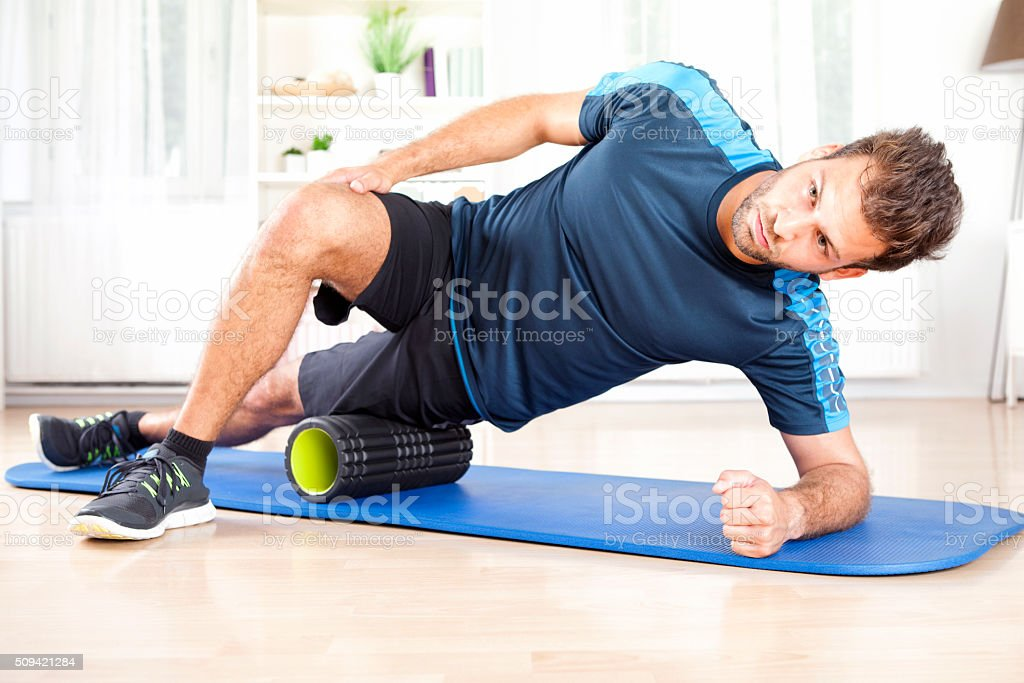 Athletic Man in Side Planking Using Foam Roller stock photo