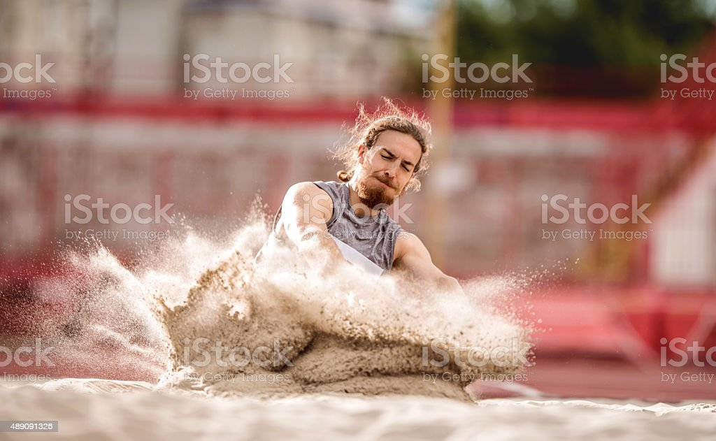 Athletic man landing in a sand after a long jump. stock photo