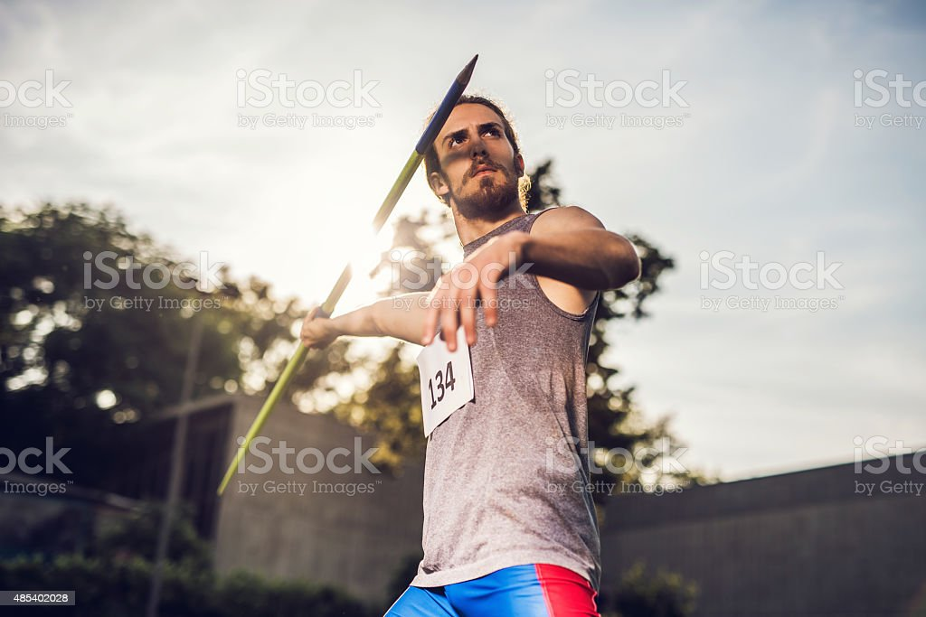Athletic man on competition ready to throw a javelin. stock photo