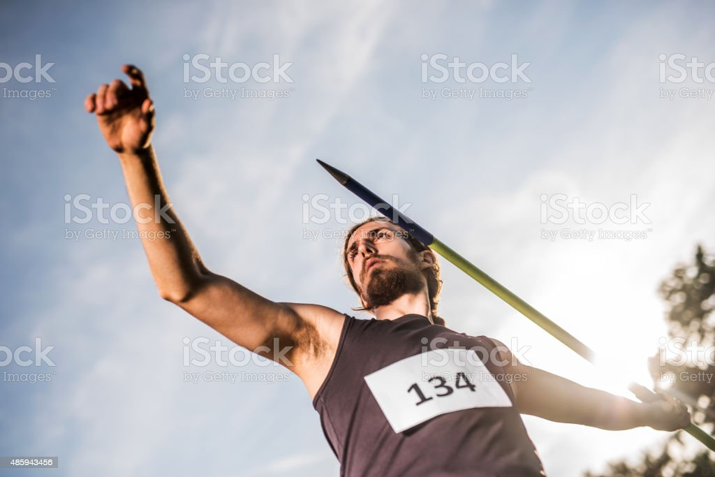 Athletic man preparing to throw a javelin against the sky. stock photo