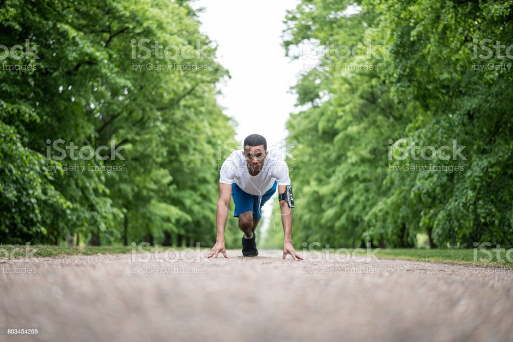 Athletic man ready for running at the park stock photo