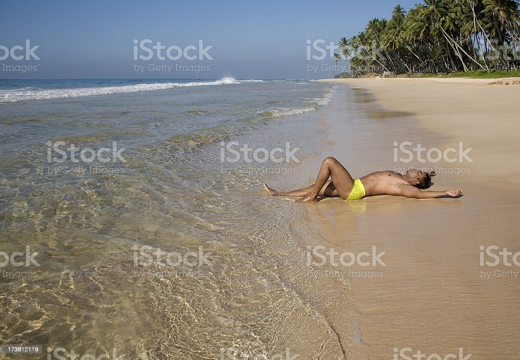 athletic man relaxing on tropical beach stock photo