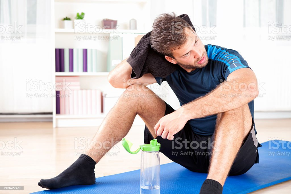 Athletic Man Resting After his Indoor Exercise stock photo