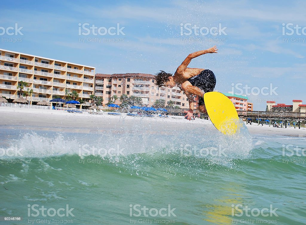 Athletic Man Skimboarding Catches Air Leaving Trail of Ocean Spray stock photo