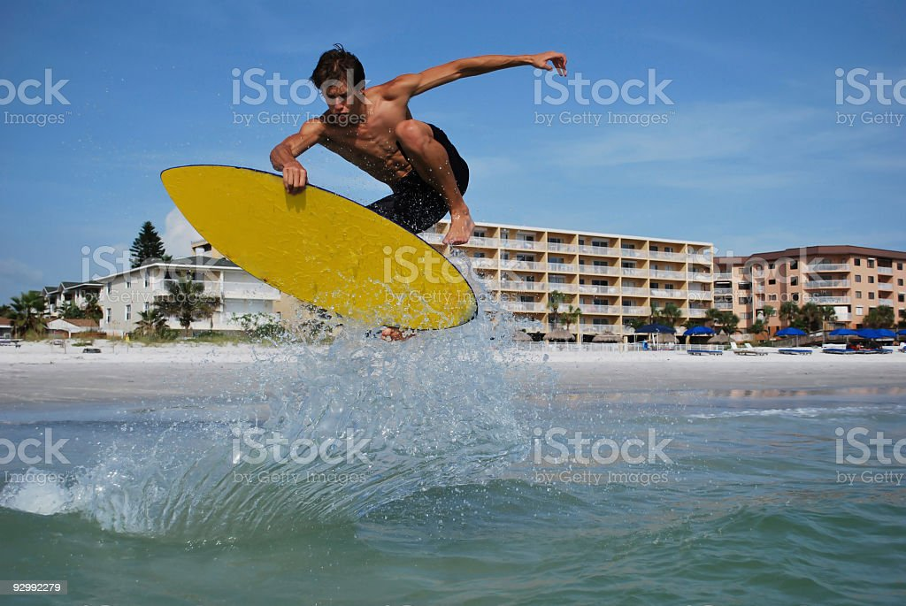 Athletic Man Skimboarding Doing a Full Turn Catches Air stock photo