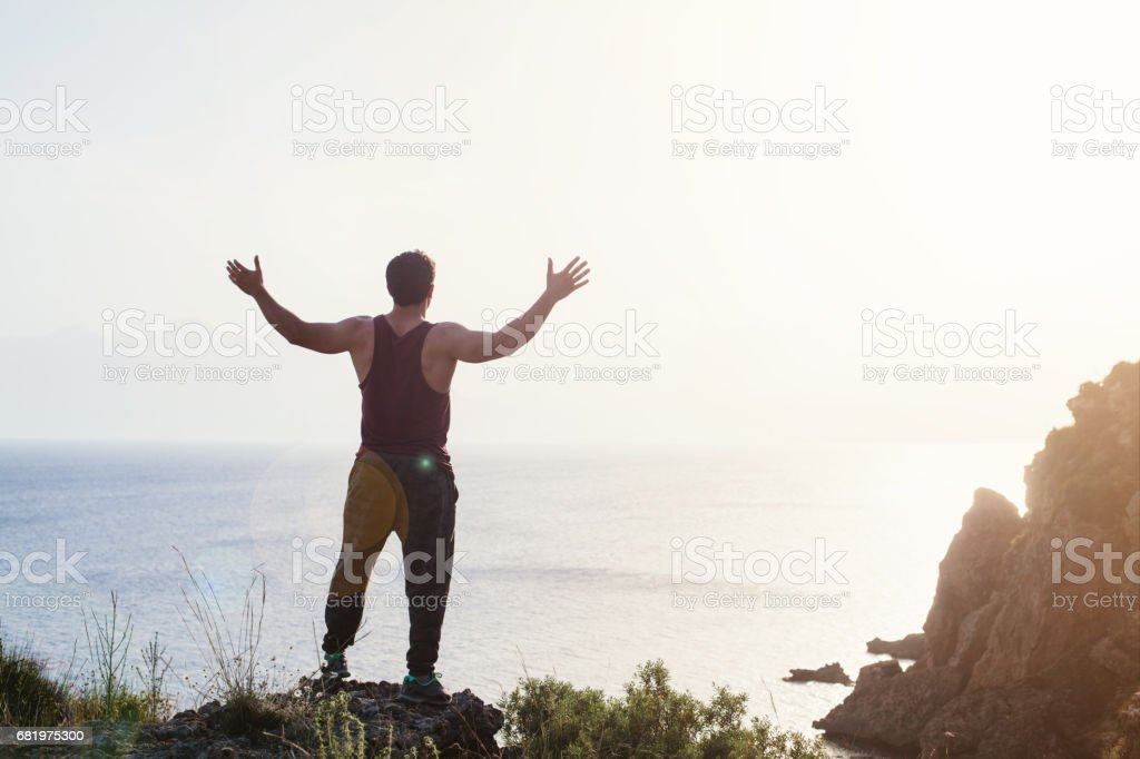 Athletic man standing on cliff stock photo