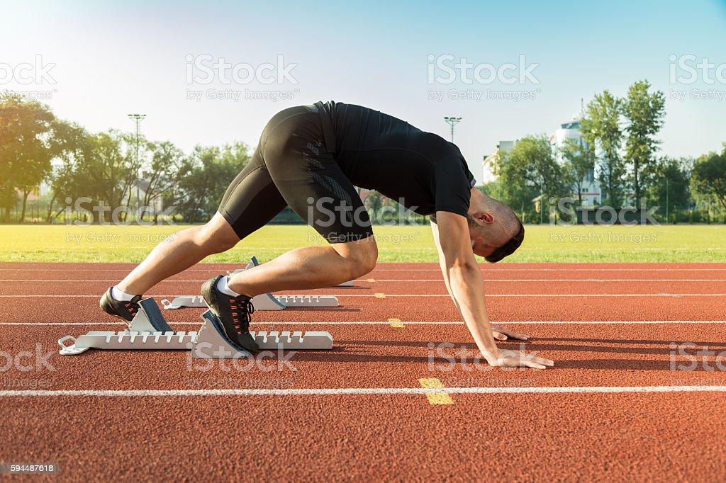 Athletic man starting jogging in sun rays stock photo