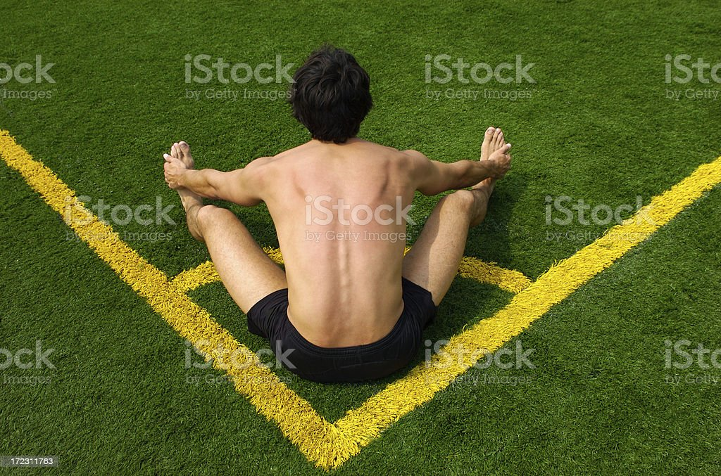 Athletic Man Stretching on Green Grass Football Field stock photo