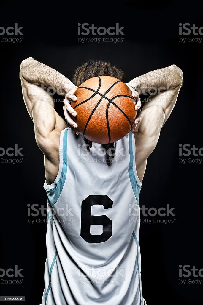 Athletic man with dreadlocks holds basketball behind head royalty-free stock photo