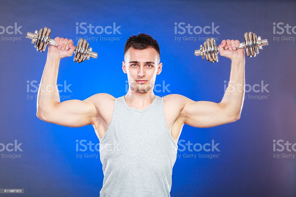 athletic man working with heavy dumbbells stock photo