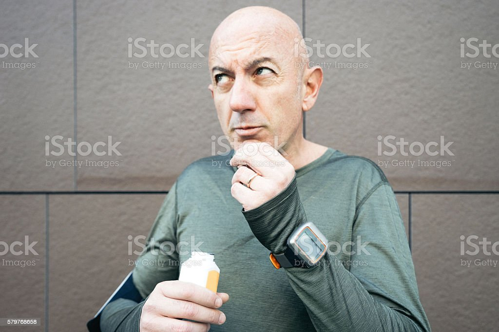 Athletic Mature Man Taking Supplements stock photo