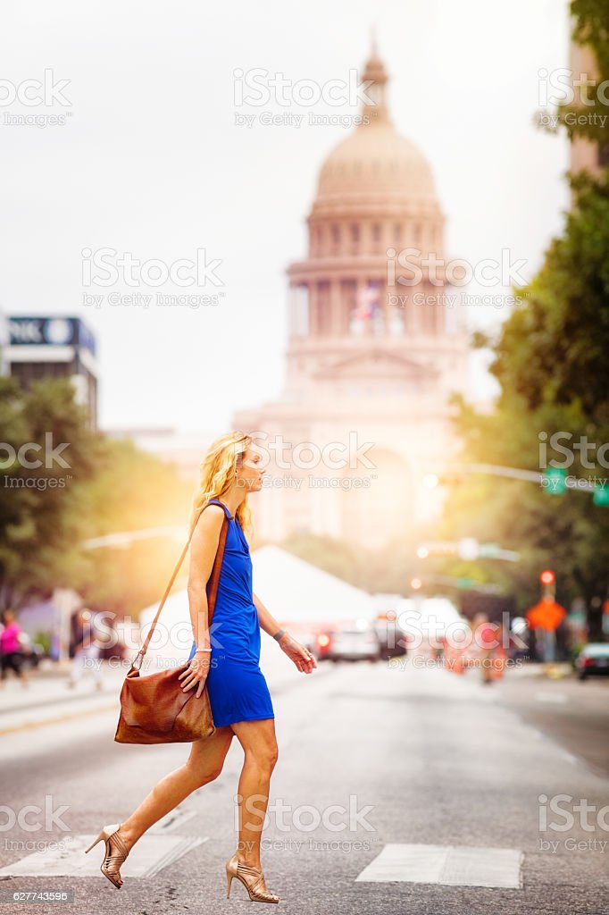 Athletic mature woman crossing Austin Congress street stock photo