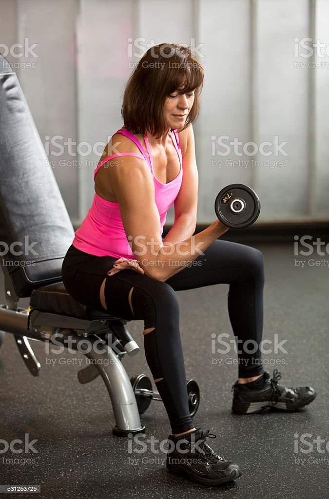 Athletic Mid Adult Woman Doing a Weightlifting Workout. stock photo