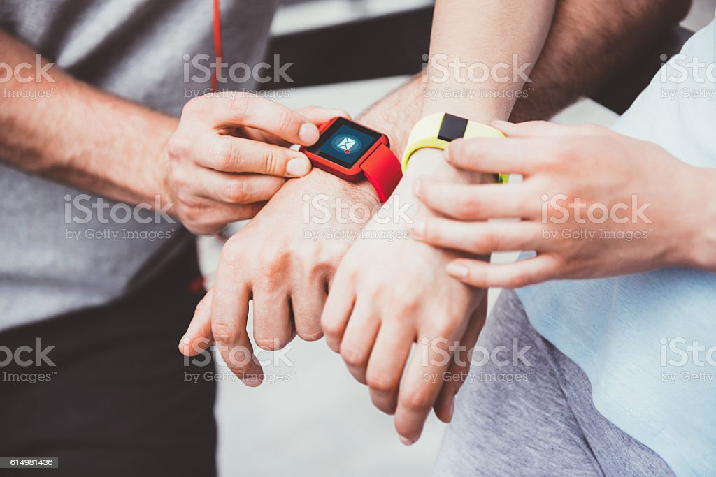 Athletic people sharing workout data from their smartwatches. stock photo
