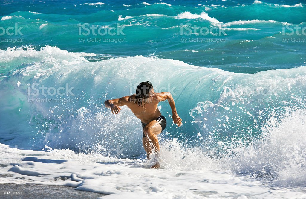 athletic single man on beach chased by big wave stock photo