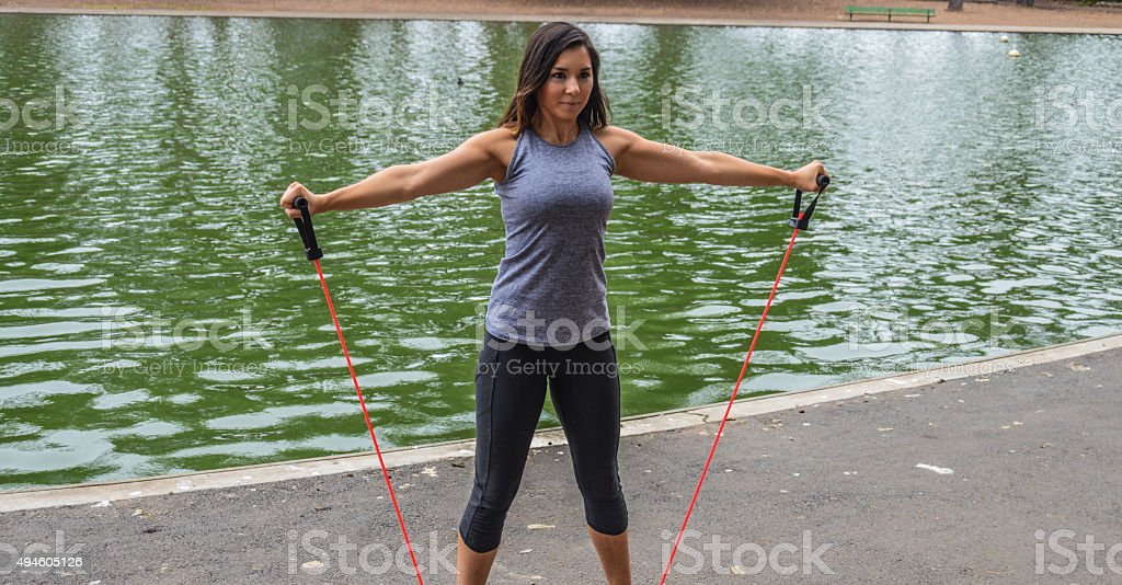 Athletic skinny woman using resistance bands stock photo