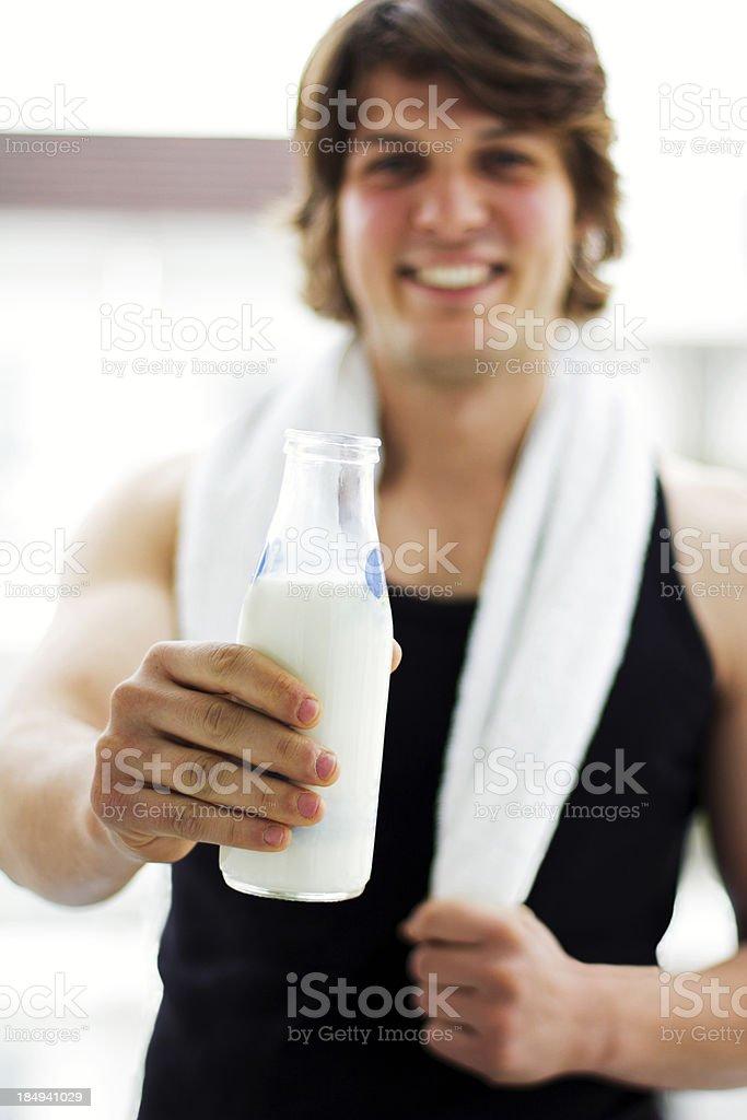 Athletic smiling man showing milk bottle royalty-free stock photo