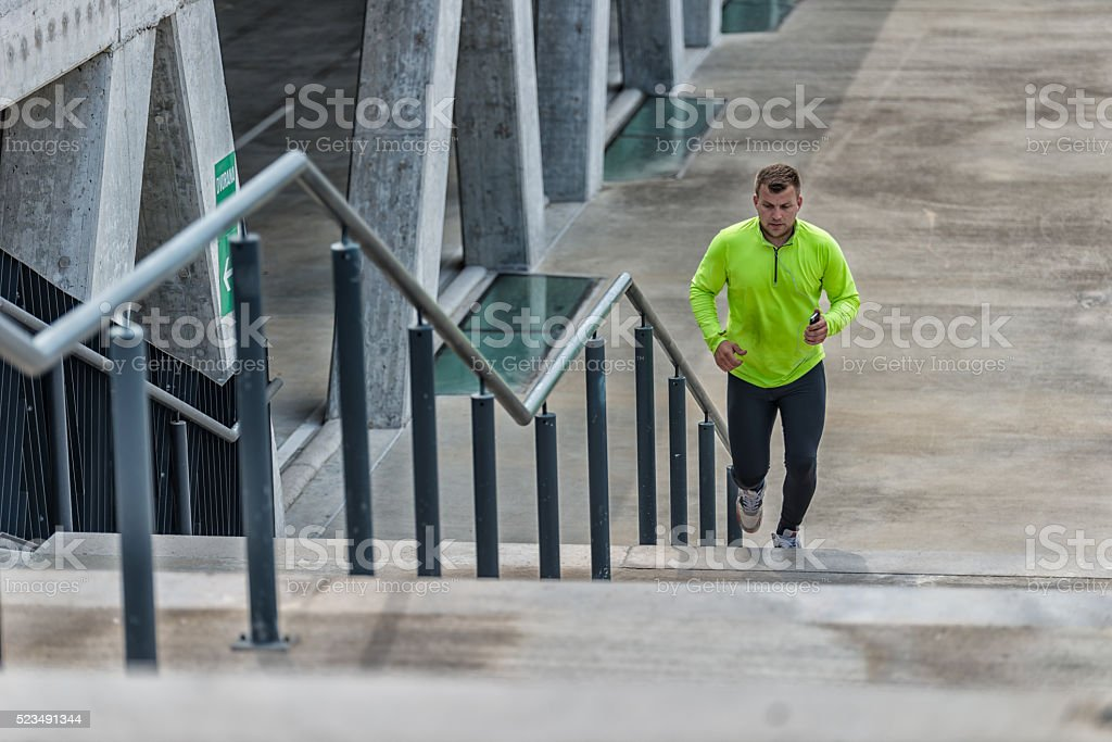 Athletic sport runner man running up stairs in urban training stock photo