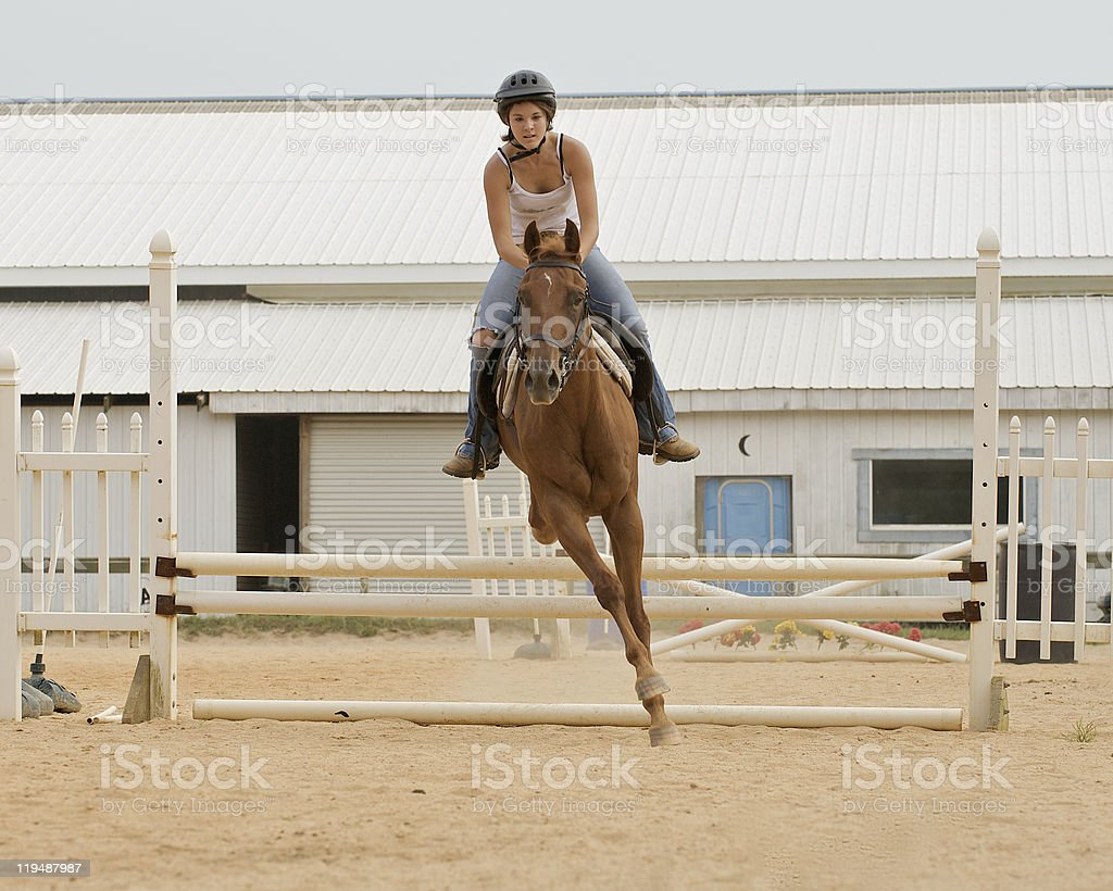 Athletic teen girl jumping a horse. stock photo