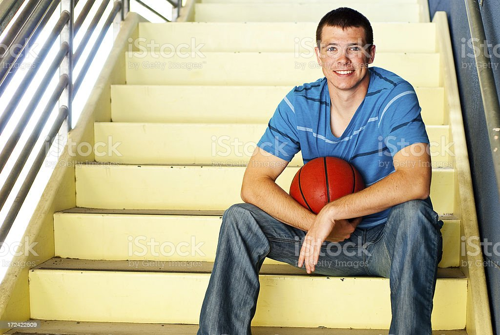 Athletic Teenage Boy Sitting with a Basket Ball royalty-free stock photo