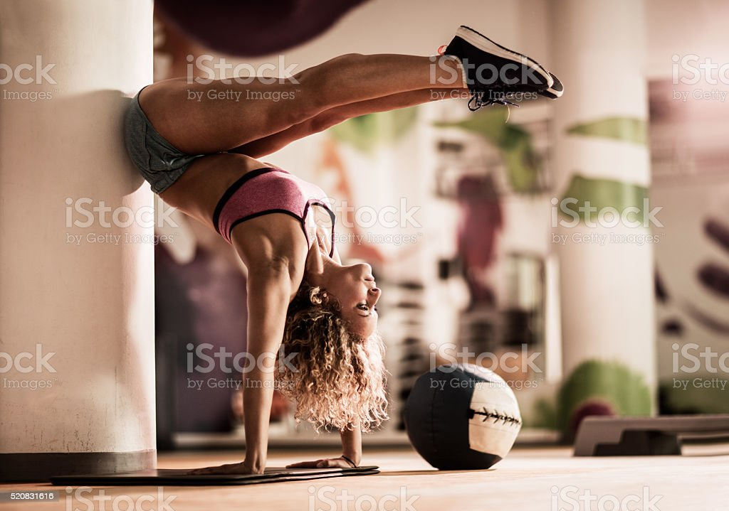 Athletic woman doing handstand in a health club. stock photo