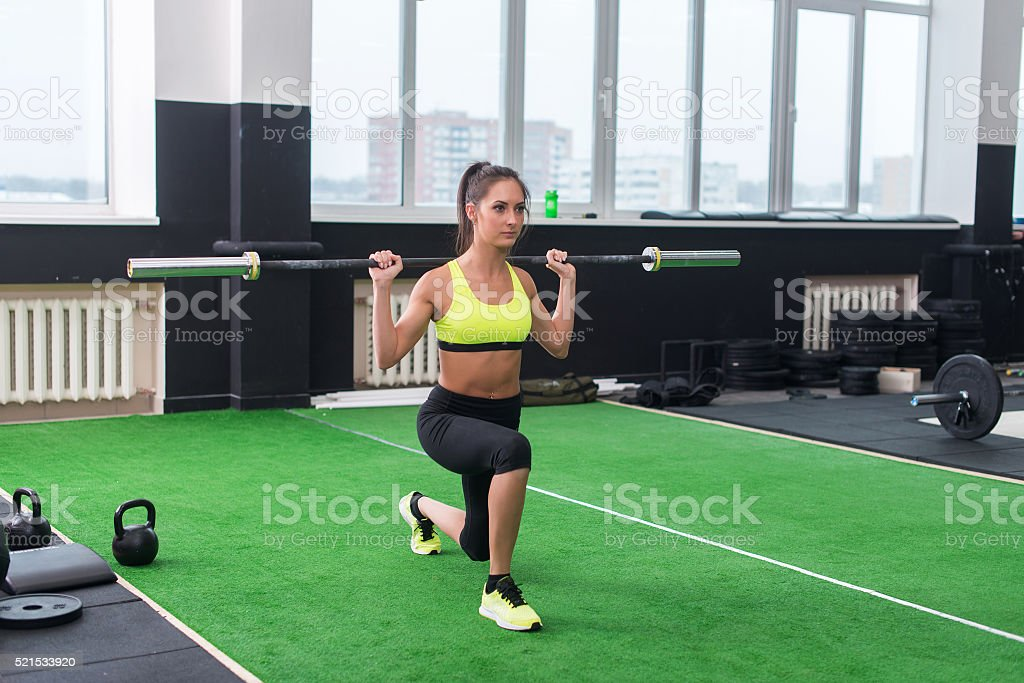 athletic woman doing lunges with barbell, working out legs and stock photo