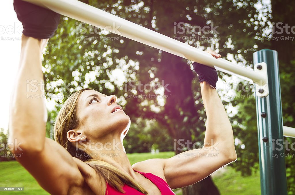 Athletic Woman Doing Pull-Ups On a Sunny Day stock photo