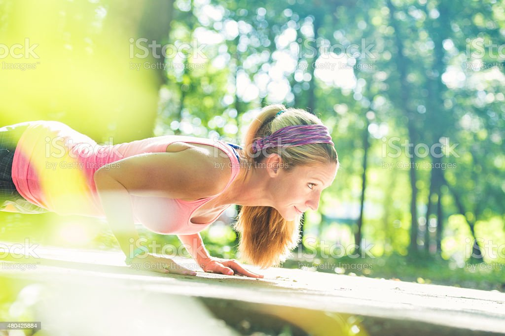 Athletic woman doing pushups during outdoor workout stock photo