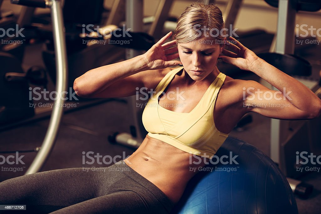 Athletic woman doing sit-up on exercise ball stock photo