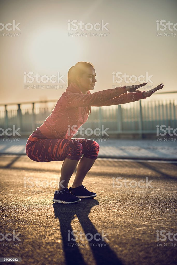 Athletic woman doing squats on a road at sunset. stock photo