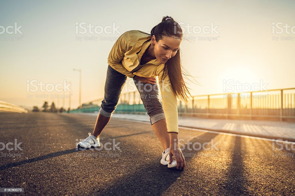 Athletic woman doing stretching exercise at sunset. stock photo