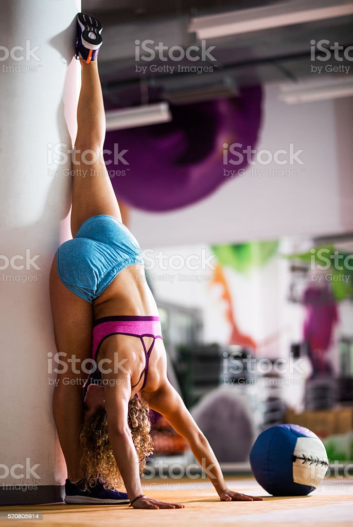 Athletic woman doing stretching exercises in a gym. stock photo