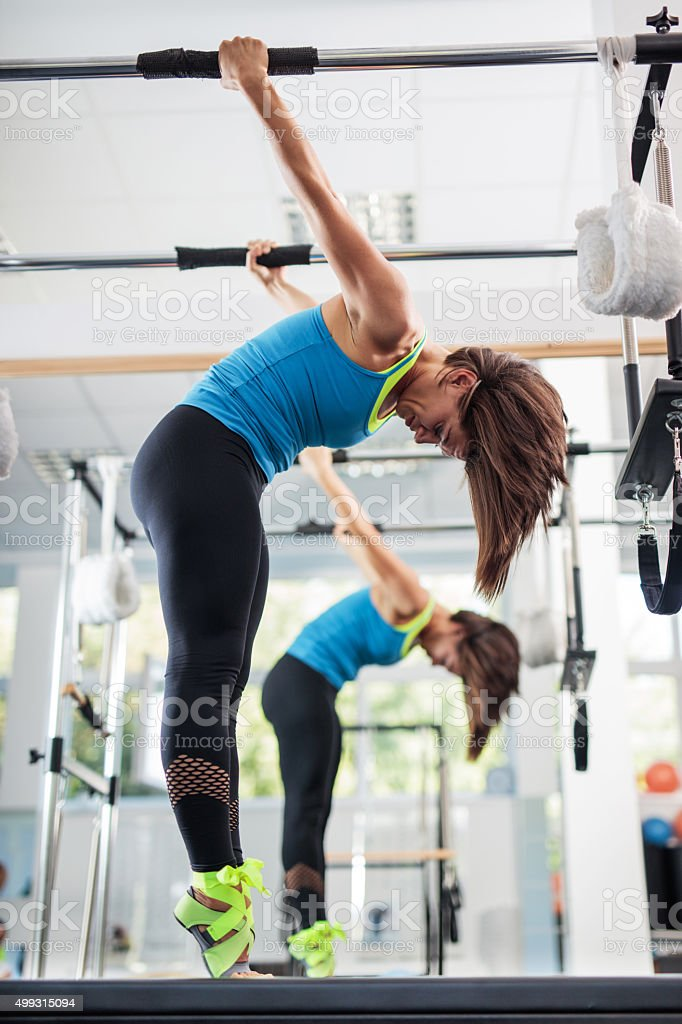 Athletic woman doing stretching exercises on Pilates machine. stock photo