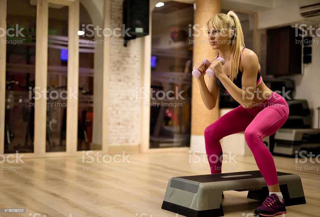 Athletic woman exercising with weights on step aerobics. stock photo