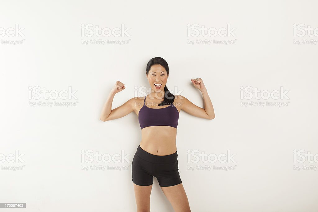 Athletic woman flexing muscles against white wall stock photo