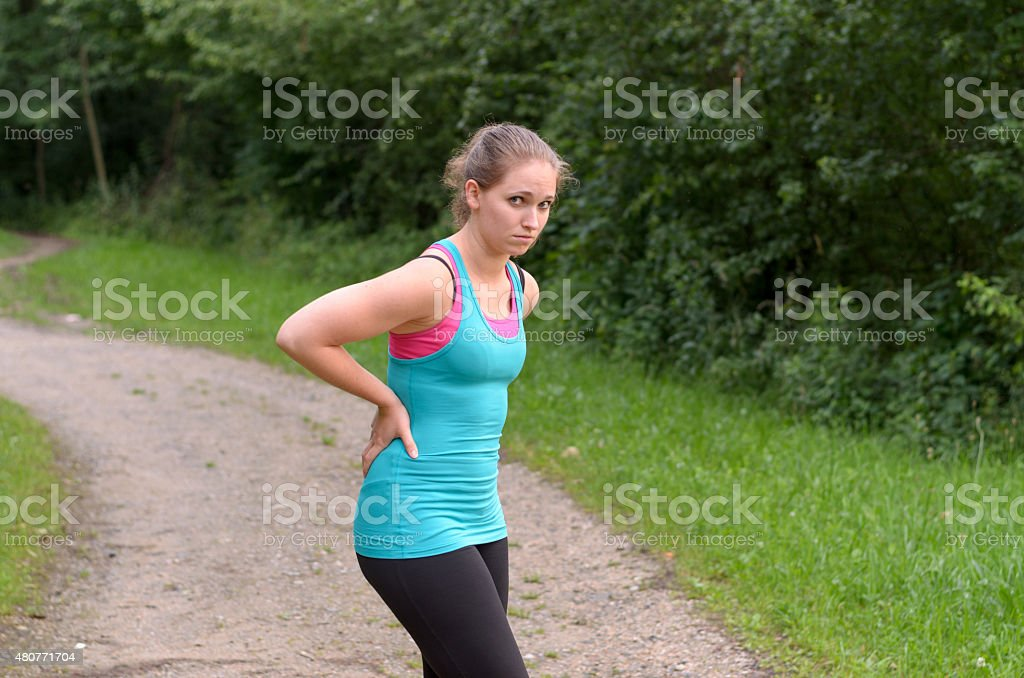 Athletic Woman Having a Back Pain While Exercising stock photo