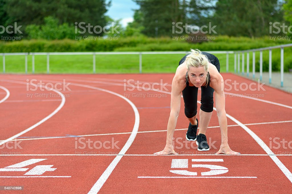 Athletic woman in the starter position on a track stock photo