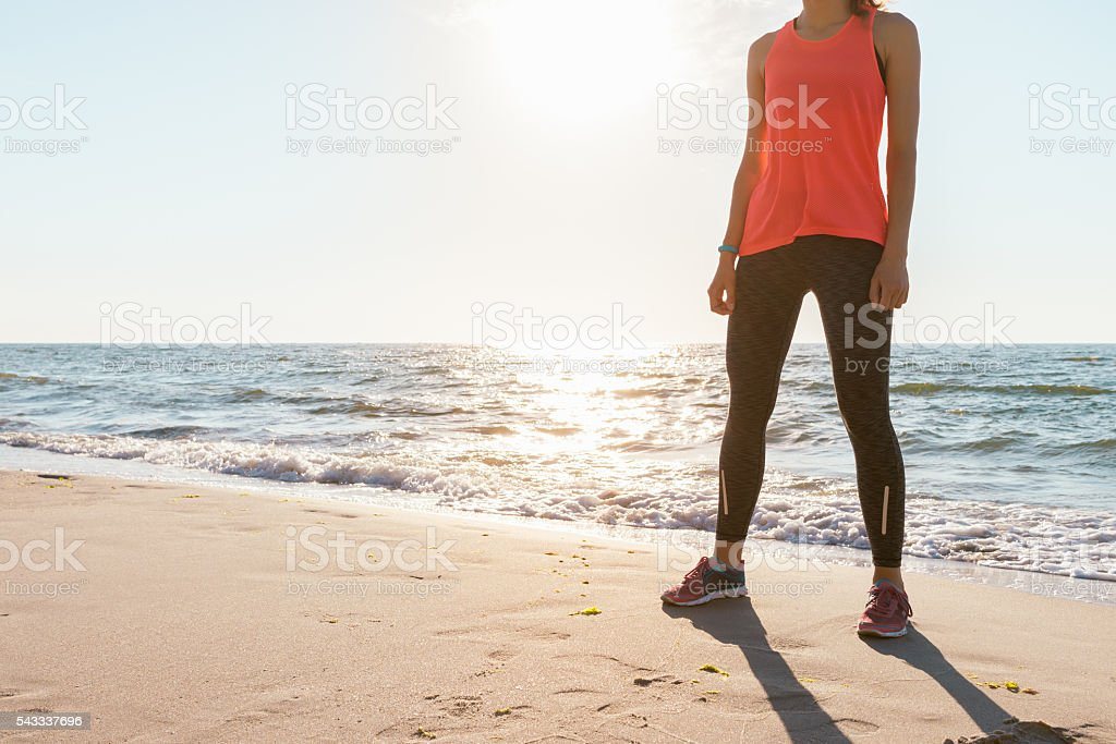 Athletic woman in T-shirt without sleeves and sneakers stock photo