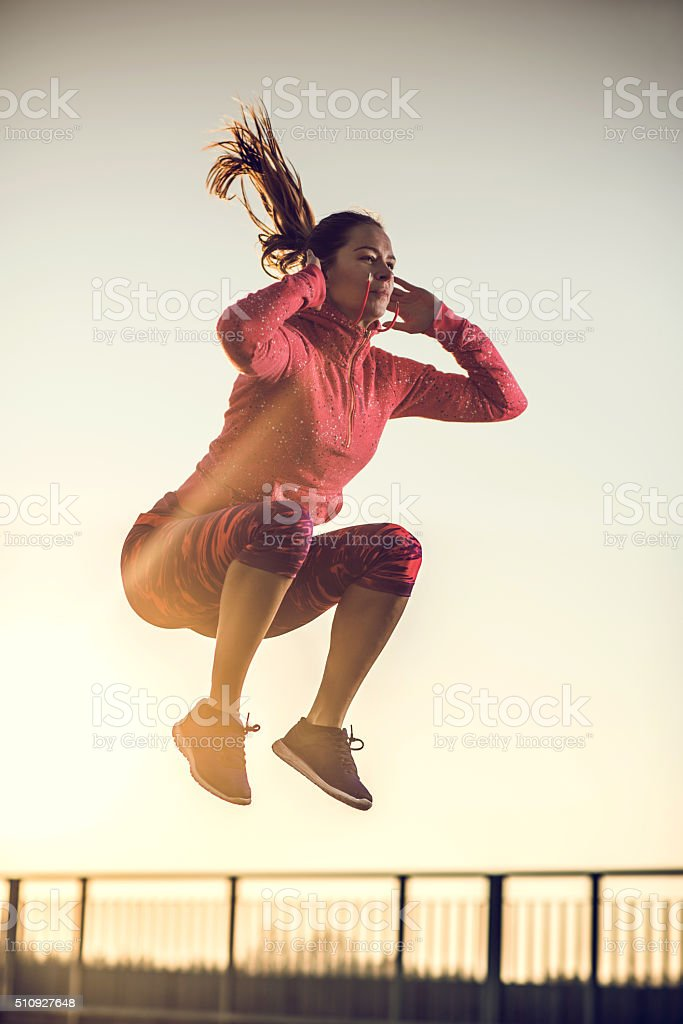 Athletic woman jumping high up at sunset. stock photo