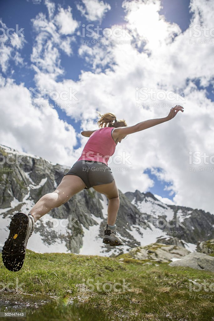 Athletic woman jumping in field stock photo