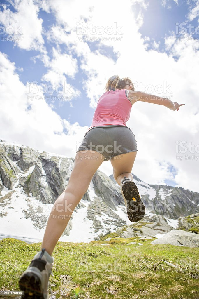 Athletic woman jumping through grass stock photo