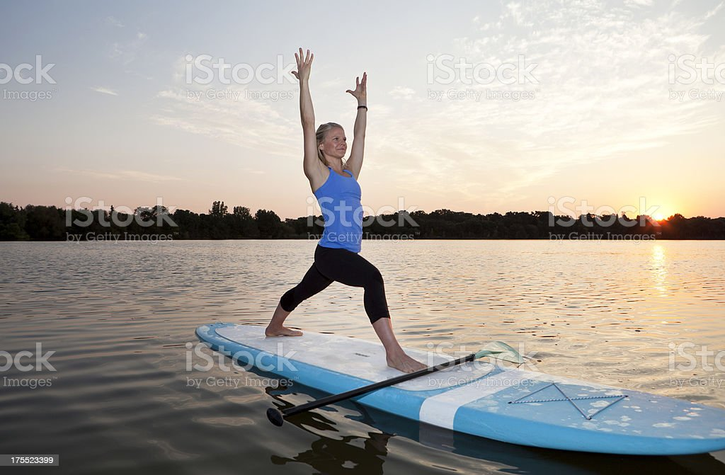 Athletic Woman Practicing Yoga on a Stand Up Paddle Board. stock photo