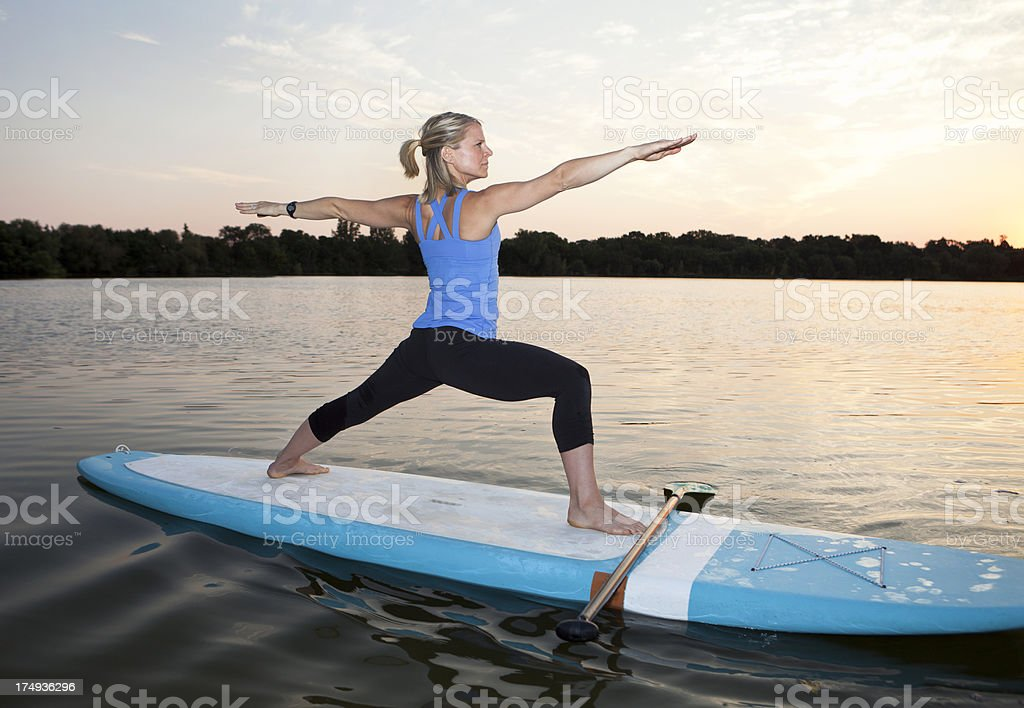 Athletic Woman Practicing Yoga on Stand Up Paddle Board. royalty-free stock photo