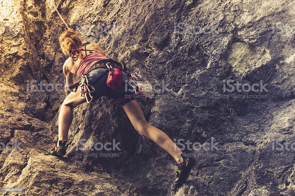Athletic woman rockclimbing at sunset stock photo