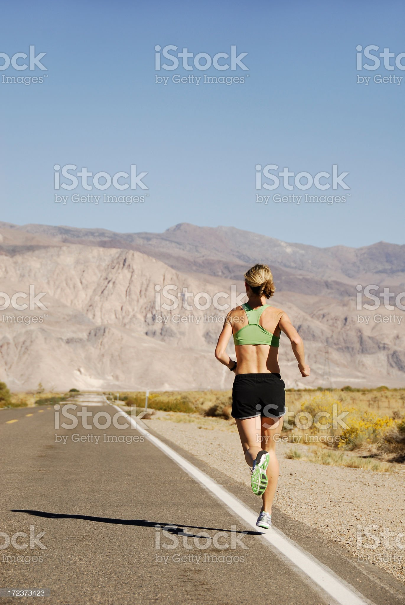 Athletic woman running along a long highway toward mountains royalty-free stock photo