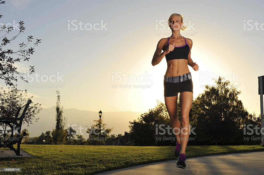 Athletic woman running in the park stock photo