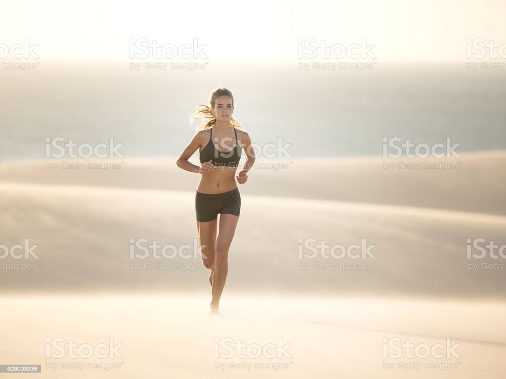 Athletic woman running over a Sand Dune, Extreme Fitness stock photo